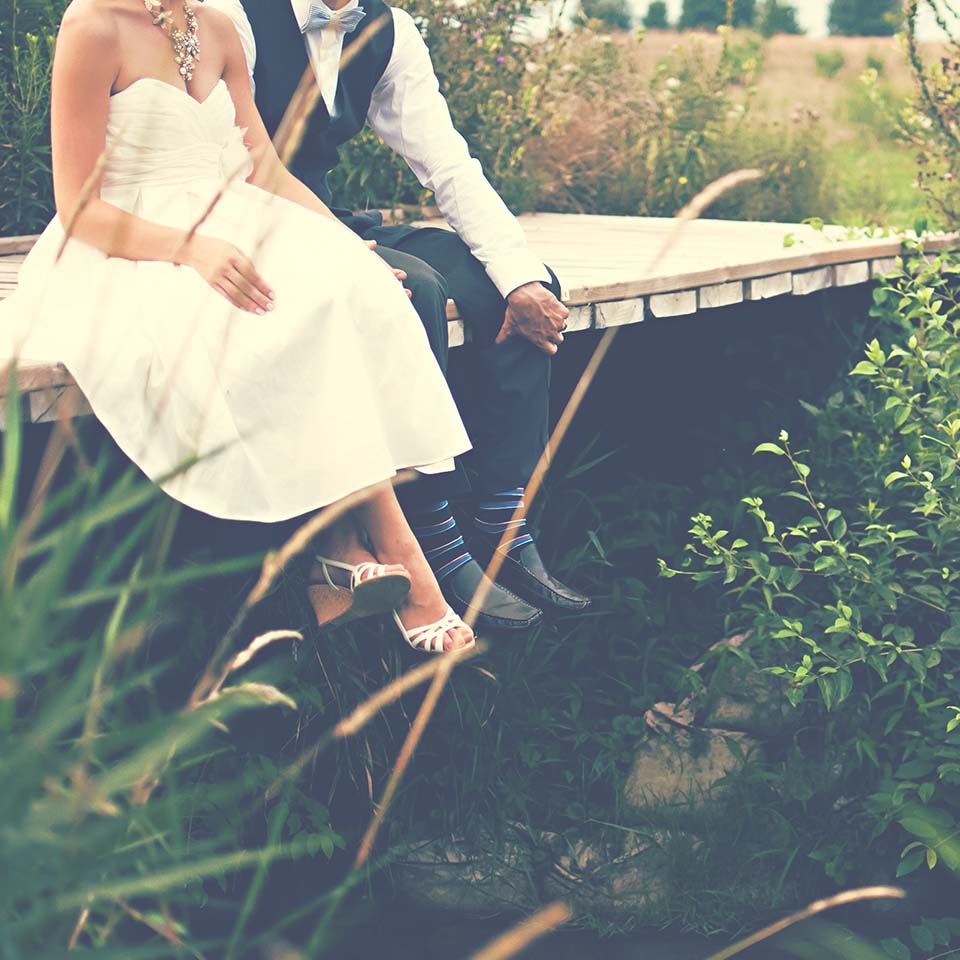 wedding couple sat on bridge